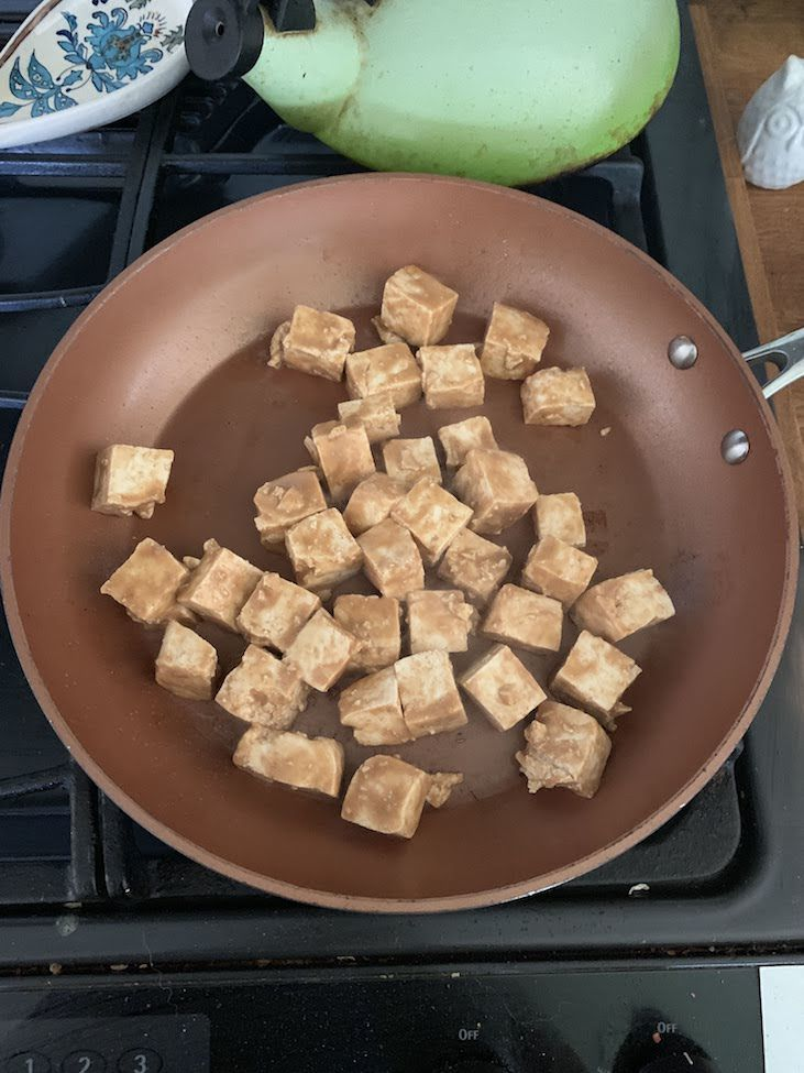 Marinated tofu cooking in frying pan